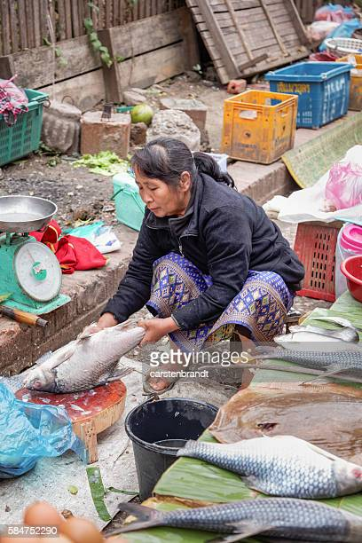 Woman cleaning fish in a street market