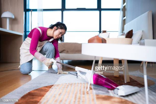woman cleaning floor with  vacuum cleaner in living room - carpet stock pictures, royalty-free photos & images