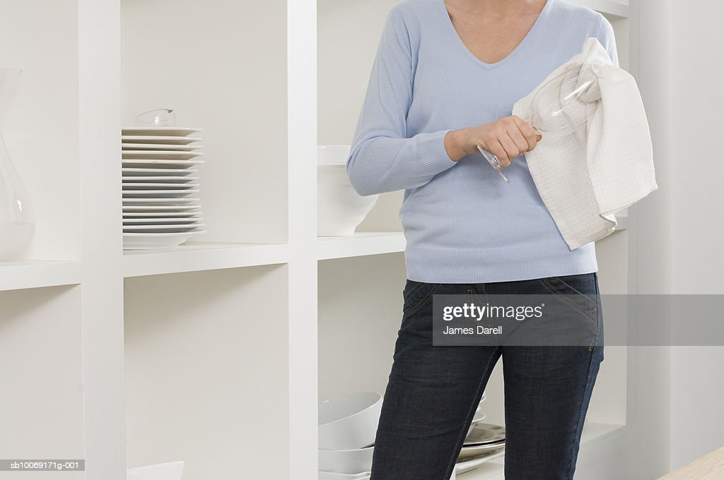 Woman cleaning glass in pantry, mid section : Stockfoto