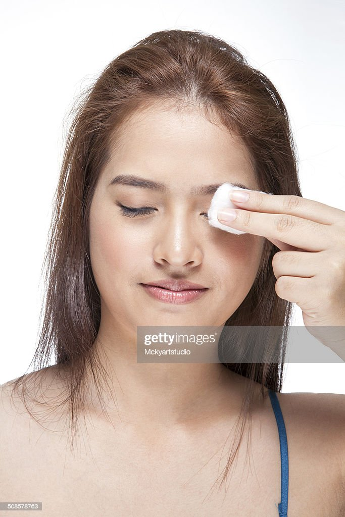 Woman cleaning her face with cotton swab : Stock Photo