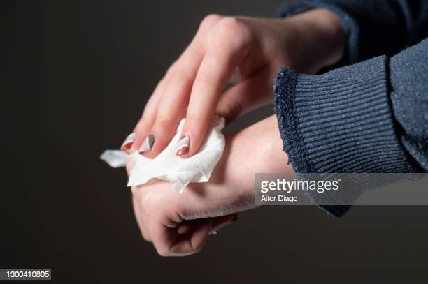 woman cleaning her skin from hand with a waterwipe. - antiseptic wipe stock pictures, royalty-free photos & images
