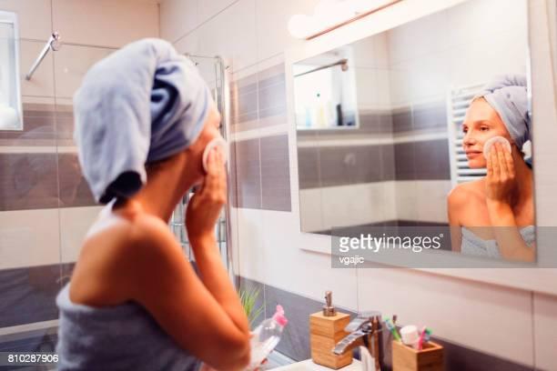 Woman cleaning her skin in bathroom.