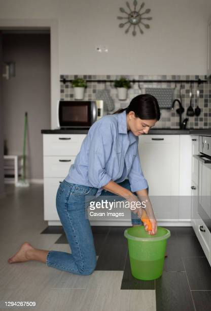 woman cleaning home and squeezing rag - daily bucket stock pictures, royalty-free photos & images