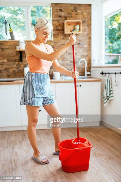 Woman cleaning house floors with mop