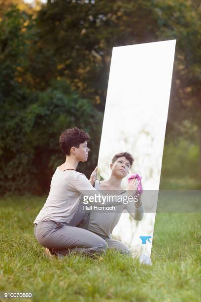 Woman cleaning mirror while crouching on grassy field at park
