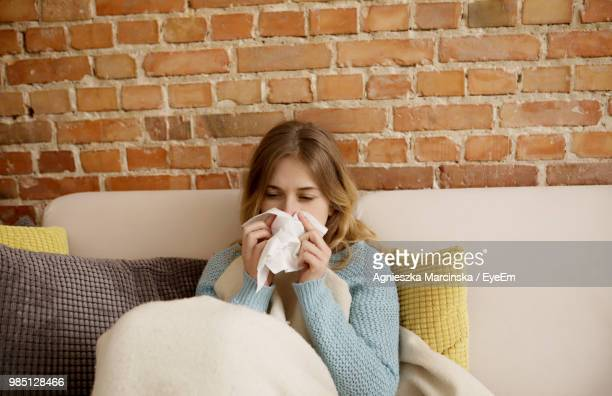 woman cleaning nose with facial tissue at home - handkerchief photos et images de collection