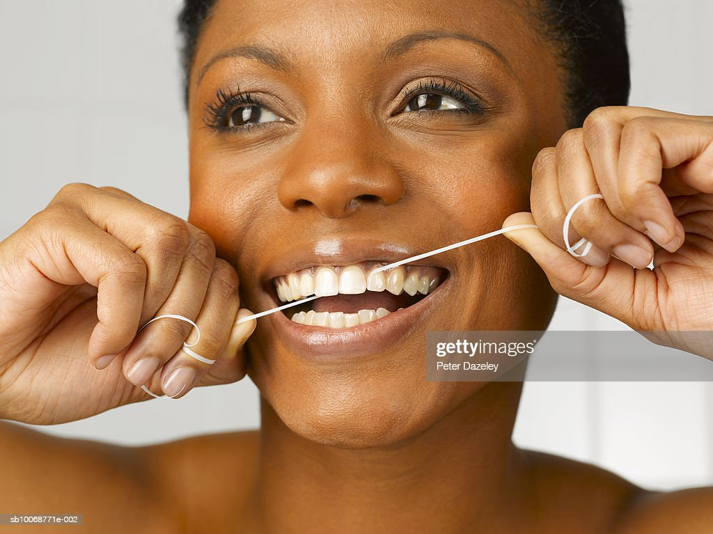 Woman cleaning teeth with dental floss, close up, studio shot : Stock Photo