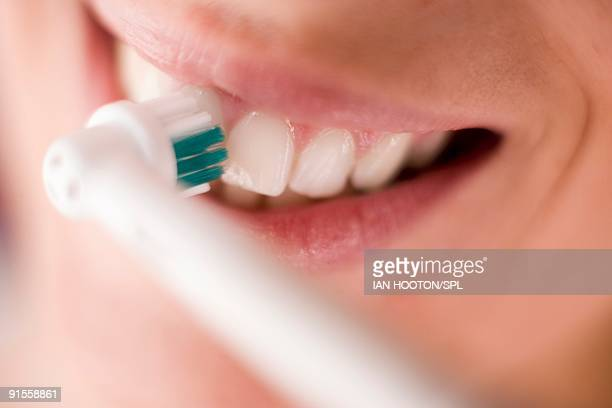 Woman cleaning teeth with electric toothbrush, close-up