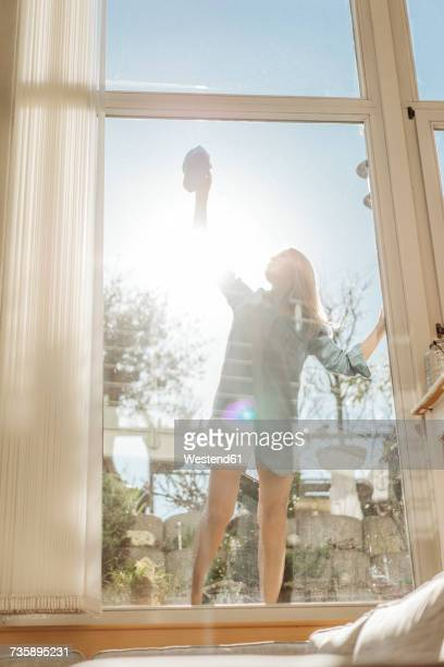 Woman cleaning the window in sunshine
