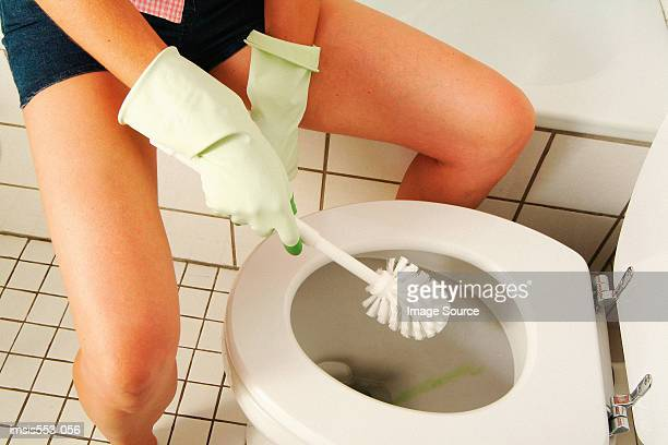Woman cleaning toilet bowl