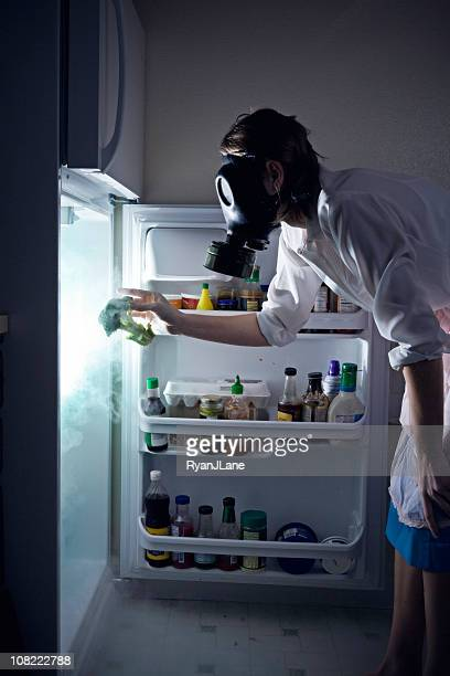 woman cleaning toxic waste glowing fridge - food contamination stock photos and pictures