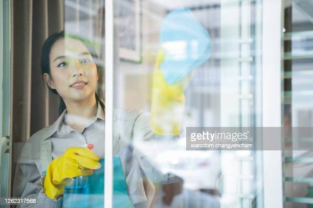 woman cleaning windows in house. - housework stock pictures, royalty-free photos & images