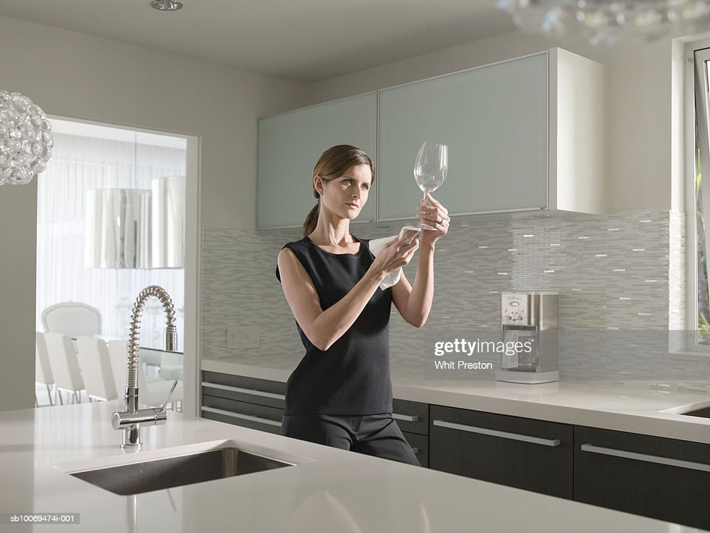 Woman cleaning wine glass in kitchen : Stock Photo