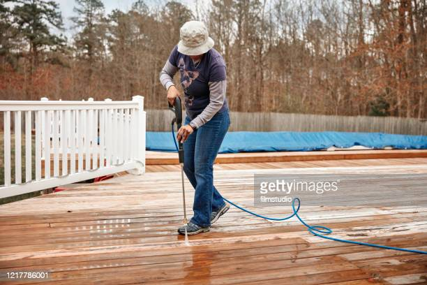 woman cleaning wooden terrace with a high water pressure cleaner - high pressure cleaning stock pictures, royalty-free photos & images