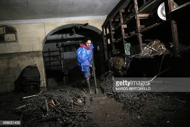 A woman cleans a house after floods in Busalla near Genoa on November 15 2014 Torrential rain closed road and rail links along the Italian Riviera as...