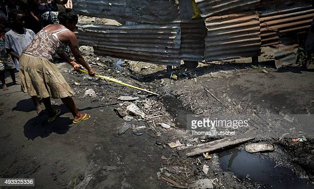A woman cleans a moat in a slum in the city area of Beira on September 28 2015 in Beira Mozambik