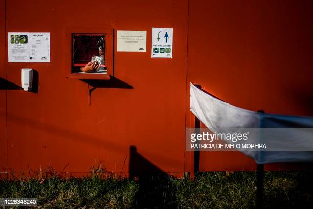 Woman cleans a protective plastic shield at a food stand during the Portuguese Communist Party Avante festival in Seixal, outskirts of Lisbon on...