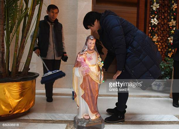 Woman cleans a religious figurine near a check-in desk for the ninth Chinese Catholic representative conference in Beijing on December 26, 2016....