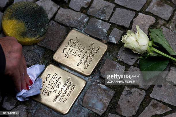 A woman cleans a 'stolperstein' or stumbling stone during a walk on occasion of the 75th anniversary of the Nazi pogrom Kristallnacht of 910 November...