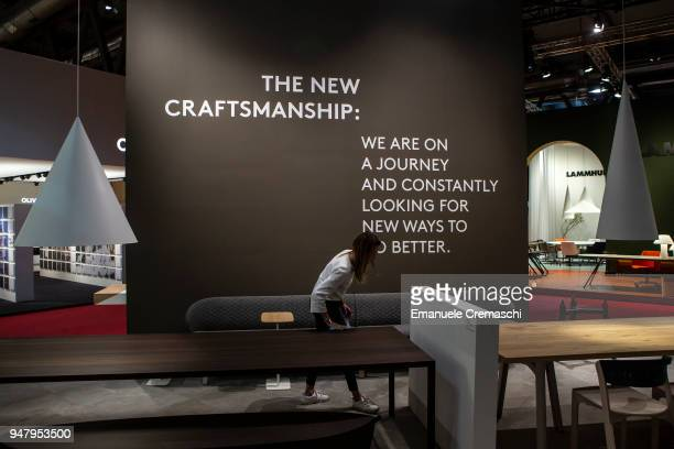 A woman cleans a table at the Arco display stand during the Salone Internazionale del Mobile at Fiera di Rho on April 17 2018 in Milan Italy Every...