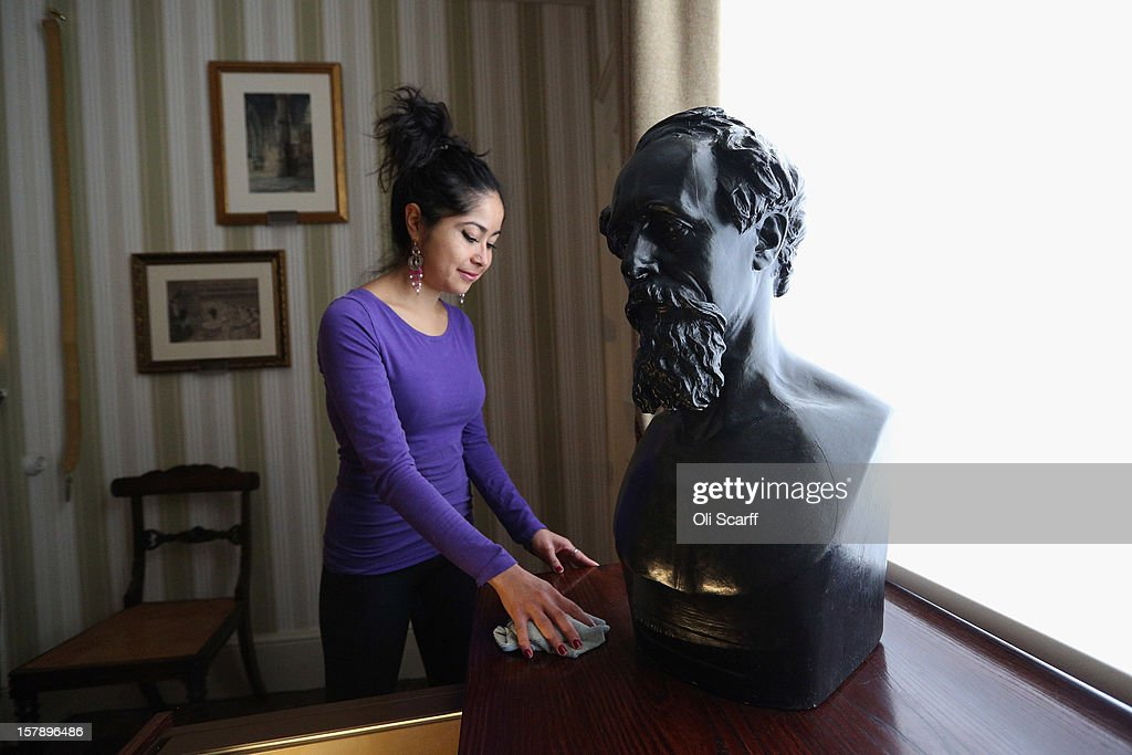 A woman cleans a table next to Dickens' death mask in a bedroom inside the Charles Dickens Museum on December 7, 2012 in London, England. The museum will re-open to the public on December 10, 2012 following a major 3.1 million GBP refurbishment and expansion programme to celebrate Dickens' bicentenary year. The museum is located in Charles Dickens' house on Doughty Street where he lived from 1837 until 1839 and in which he wrote many novels including Oliver Twist and Nicholas Nickleby.