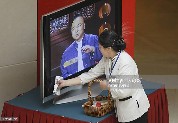 Woman cleans a television at the press centre for the 17th National Congress of the Communist Party of China in Beijing, 11 October 2007. Prime time...