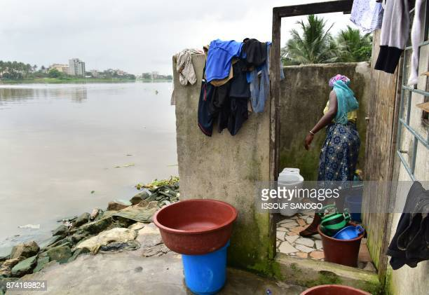 A woman cleans a toilet in an impoverished neighbourhood near a lagoon in Abidjan on November 14 2017 / AFP PHOTO / ISSOUF SANOGO