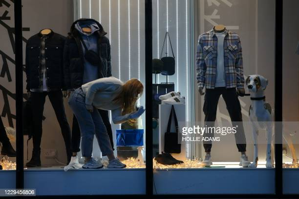 Woman cleans a window at the River Island store on Oxford Street in central London on November 4 as the country prepares for a second novel...