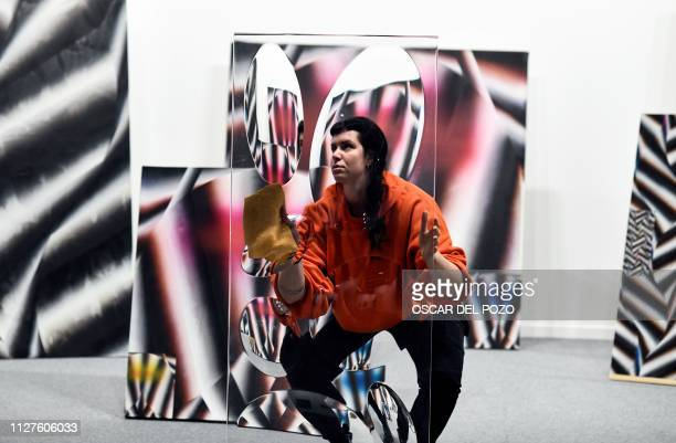 A woman cleans an installation as gallery workers prepare artworks to be exhibited at the International Contemporary Art Fair in Madrid on February...