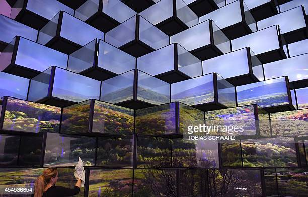 A woman cleans an installation of television sets at the booth of Vestel during the first press day of the consumer electronics trade fair...