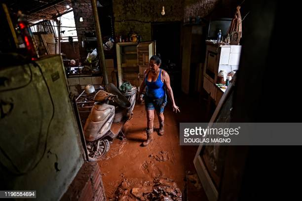 Woman cleans at a restaurant after the overflowing of the Das Velhas River in Sabara, Belo Horizonte, Minas Gerais state, Brazil, on January 26 after...