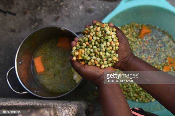 A woman cleans beans and vegeables in a bucket of water as she prepares lunch near her house in the neighborhood of Jalousie in the commune of Petion...