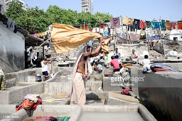 Woman cleans clothes in a traditional outdoor washing area in Mumbai