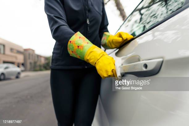 woman cleans exterior car door handle with disinfectant wipe - vehicle door stock pictures, royalty-free photos & images