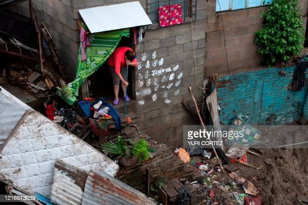 Woman cleans her house damaged by the overflowing of a creek due to the torrential rains caused by the passage of tropical storm Amanda in San...