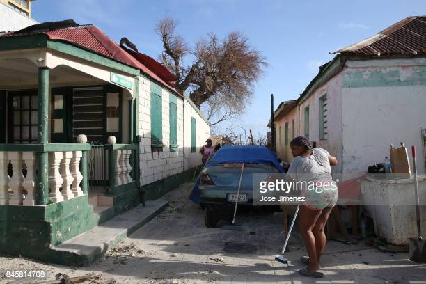 A woman cleans in front of her property on September 11 2017 in Philipsburg St Maarten The Caribbean island sustained extensive damage from Hurricane...