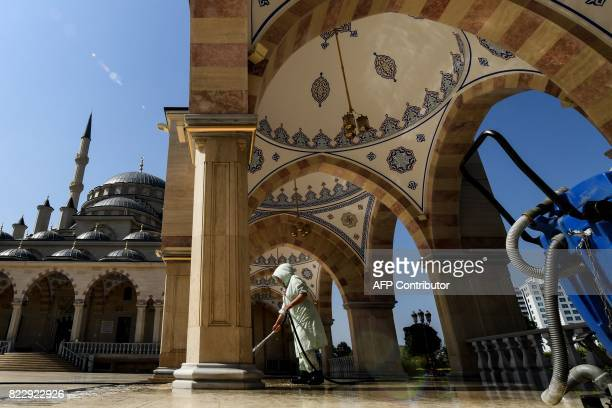 A woman cleans inside the Heart of Chechnya Akhmad Kadyrov Mosque one of the largest mosques in Russia in central Grozny on July 26 2017 / AFP PHOTO...