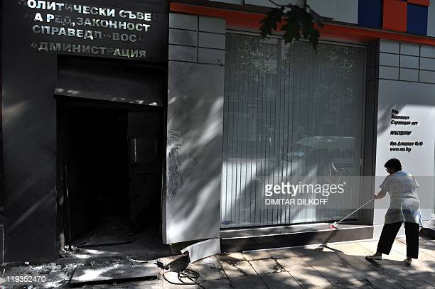 A woman cleans near the entrance of the headquarters of the rightwing populist faction Order law and justice after an explosion in Sofia on July 19...