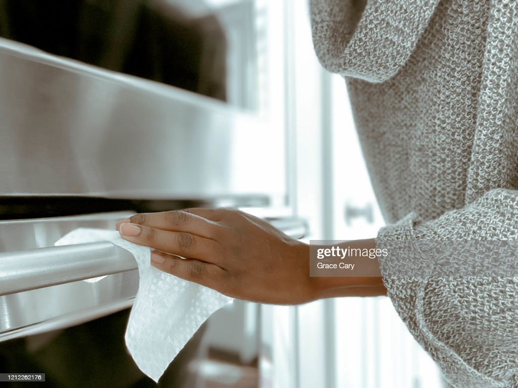 Woman Cleans Oven Handle Using Disinfectant Wipe : Stockfoto