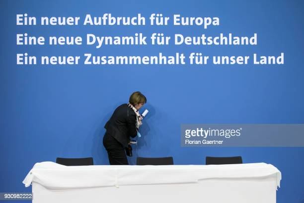 Woman cleans the background before the signing of the coalition agreement between Christian Democratic Union of Germany , Christian Social Union of...