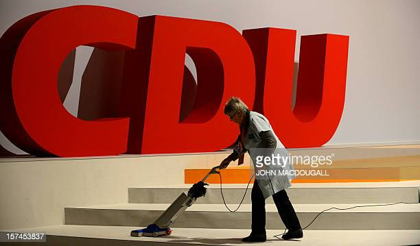 A woman cleans the carpet in front of a party logo as preparations are under way for the upcoming congress of the ruling conservative Christian...