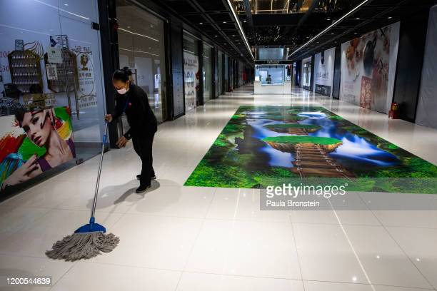 Woman cleans the floor of a shopping mall while many shops remain closed as Chinese residents of Cambodia who left for the New year are not allowed...