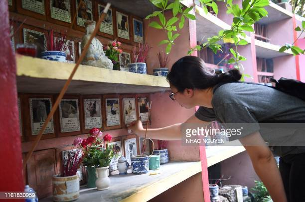 A woman cleans the plague of her cat at Te Dong Vat Nga pagoda which means all lives are equal a pet cemetary in Hanoi on August 15 2019 Sausages...