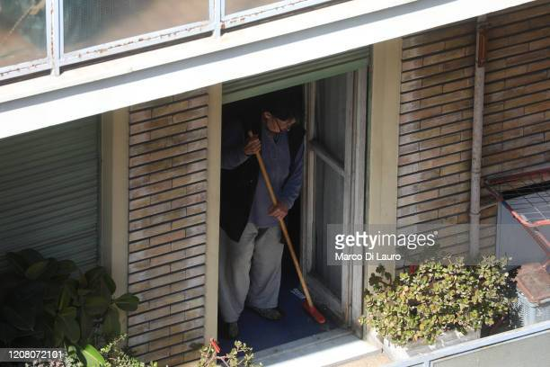 A woman cleans the terrace of her apartment during lockdown on March 23 2020 in Rome Italy As Italy extends its nationwide lockdown to control the...