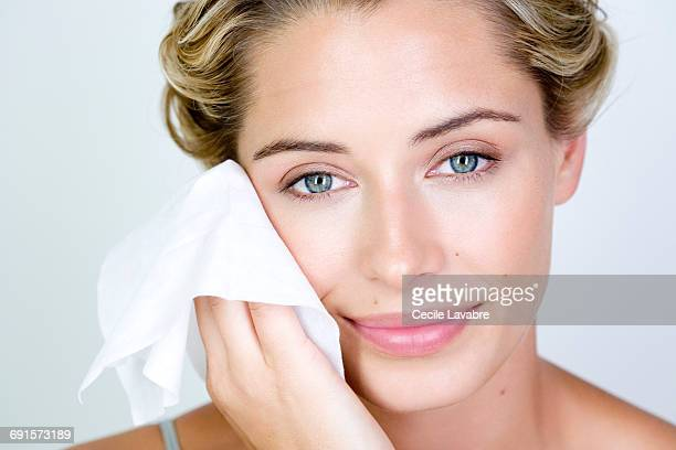 Woman cleansing face with wipe