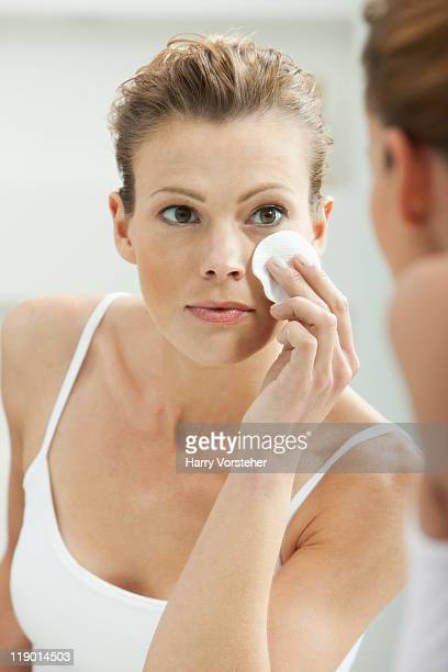 Woman cleansing her face in bathroom