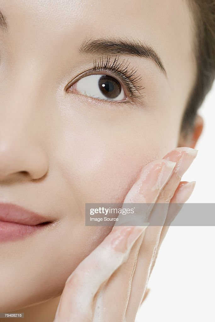 Woman cleansing her face : Stock Photo