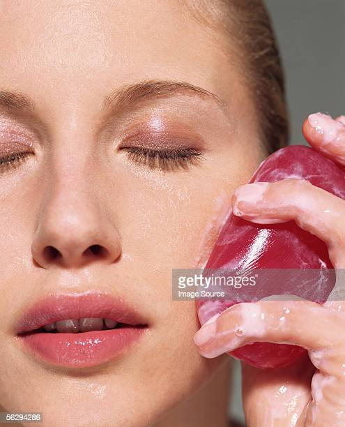 Woman cleansing her face with soap
