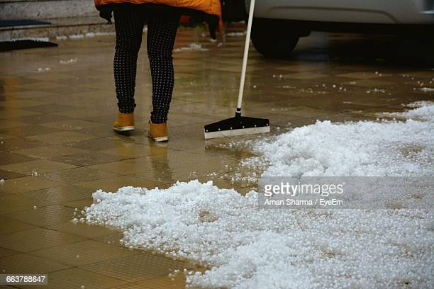 Woman Clearing Hail With Mop