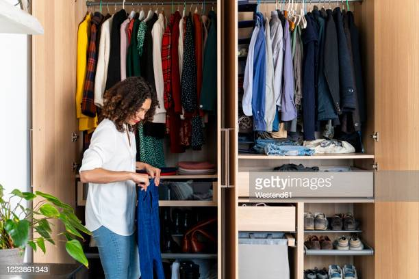 woman clearing out her wardrobe - organization stock pictures, royalty-free photos & images